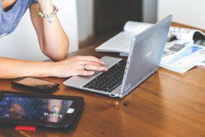 Frau mit Laptop, Tablet und Smartphone