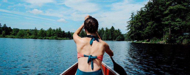 Frau rudert Boot über einen See