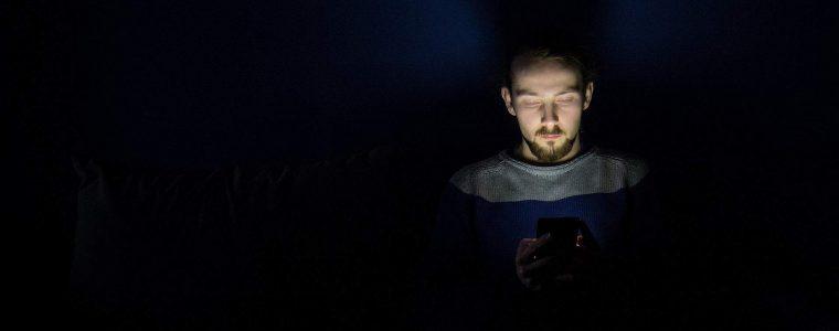 Junger Mann nutzt Smartphone im Dunkeln